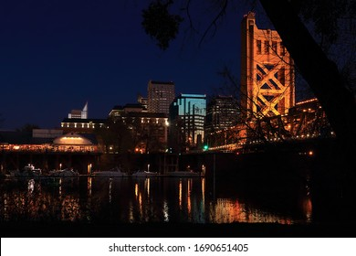 Downtown skyline of Sacramento, CA/USA taken from across the Sacramento River in this blue hour shot at dusk.  The brightly lit historic Tower Bridge and a popular restaurant in Old Town are in view.