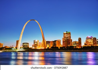 Downtown St Louis, MO with the Old Courthouse and the Gateway Arch at sunset