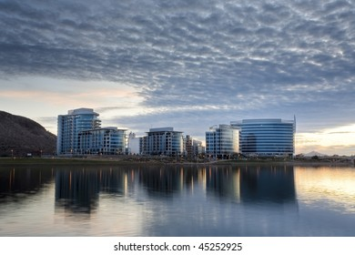 Downtown Tempe office and condo buildings with Tempe Town Lake in the foreground.