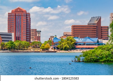 Downtown Toledo Ohio is filled with multi colored architecture that sits alongside the Maumee River. Ducks float in the water and sit on the island.