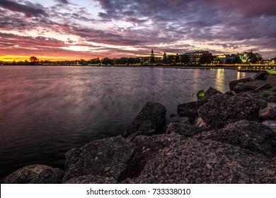 Downtown Traverse City Coastal Sunrise. Morning sunrise over the rocky coast of Grand Traverse Bay with downtown Traverse City, Michigan in the background.