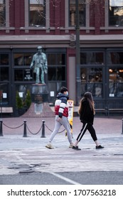 DOWNTOWN VANCOUVER, BC, CANADA - APR 01, 2020: A couple in Gastown wearing medical facemasks in front of the Gassy Jack statue amid the Covid 19 pandemic.