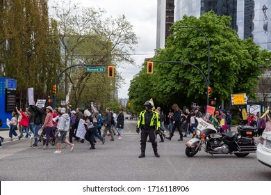 DOWNTOWN VANCOUVER, BC, CANADA - APR 26, 2020: Anti lockdown protesters march in defiance of the government imposed quarantine measures taken to slow the spread of the Covid 19 virus with police