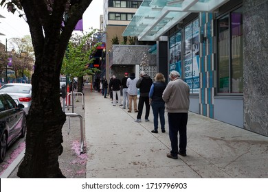 DOWNTOWN VANCOUVER, BC, CANADA - APR 26, 2020: Customers in downtown Vancouver line up and wait to get into a store due to capacity restrictions in light of the Covid 19 pandemic.
