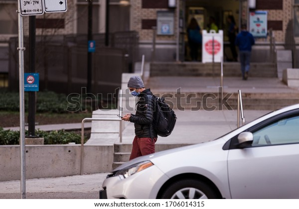 DOWNTOWN VANCOUVER, BC, CANADA - APR 01, 2020: Person wearing a medical face mask outside St Pauls hospital in Vancouver during the Covid 19 pandemic.