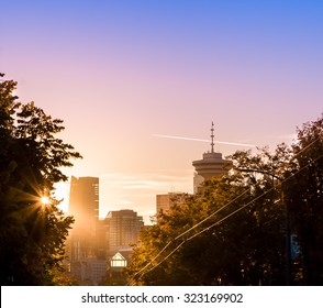 Downtown Vancouver behind the trees at sunset.