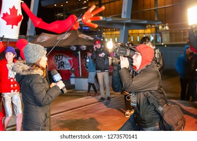 Downtown Vancouver, British Columbia, Canada - December 31, 2018: Global News Reporter, Sophie Lui, is reporting on New Years Eve at Jack Poole Plaza.