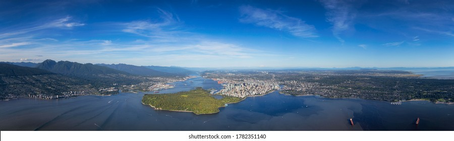 Downtown Vancouver, British Columbia, Canada. Aerial Panoramic View of the Modern Urban City, Stanley Park, Harbour and Port. Viewed from Airplane Above during a sunny day.