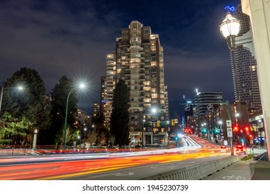 Downtown Vancouver cityscape at night. Traffic scene at Burrard Street Bridge and Pacific St crossing. British Columbia, Canada.