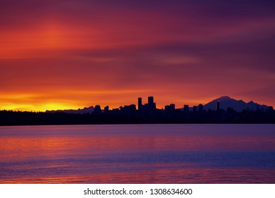 Downtown Vancouver at sunrise with Mt Baker in the background and Burrard Inlet in the foreground, BC, Canada