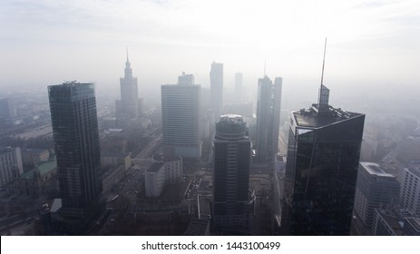Downtown Warsaw skyline. Aerial view on modern skyscrapers in the fog. Modern skyscrapers are illuminated with the sure sun at sunset.