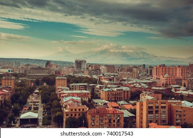 Downtown Yerevan cityscape. Travel to Armenia. Tourism industry. Mount Ararat on background. Cloudy sky. Armenian architecture. City tour. Urban landscape. Street view. Sightseeing concept. Copyspace.