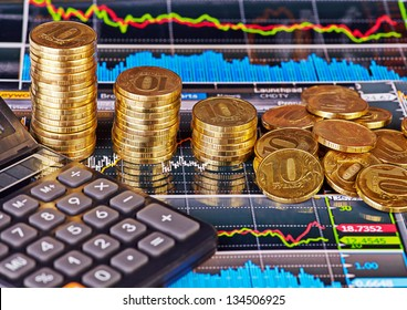 Downtrend stacks of golden coins, calculator and financial chart as background. Selective focus