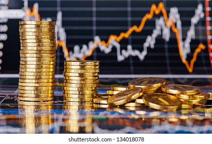 Downtrend stacks of golden coins and  financial stock charts as background. Selective focus