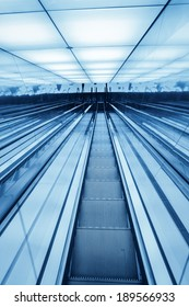 downward escalator ,abstract space in a blue glass building