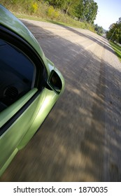 A downward side view of a green car driving along a country road.  Side of car, side mirror, side window, and road are visible.