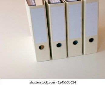 Downwards sideview towards a group of 4 folders for office papers standing on a clean white desk