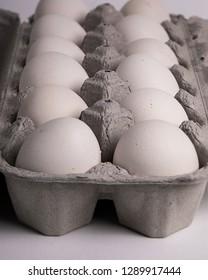 A dozen backyard chicken eggs in a  grey egg carton.