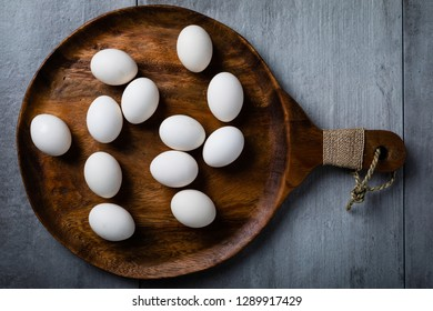 A dozen fresh white checken eggs placed on a wood serving platter taken from over head.