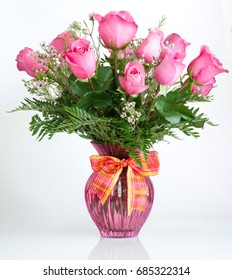 A dozen pink roses in a pink glass vase with a ribbon.