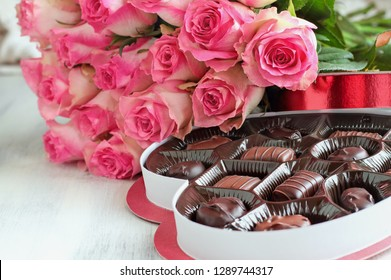 Dozen soft pink rose flowers with a heart shaped box of chocolate candy for Valentine Day over a wood background.