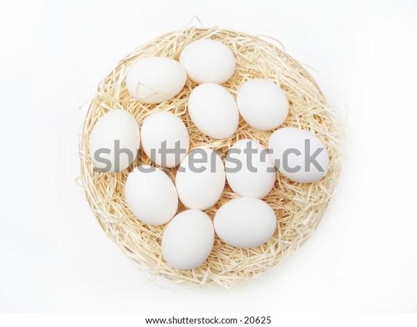 A dozen white eggs in a basket.