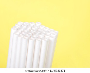 Dozens of biodegradable eco-friendly paper straws bundled together facing forward and upwards on a yellow background with copy space. Many cities are now banning single use plastic straws.