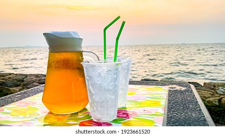 Draft beer with a glass of ice with the sunset time. A beautiful picture Beside the beach with the sea breeze blowing