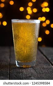 draft beer in a glass on dark blurry lights - Shutterstock ID 1245398584