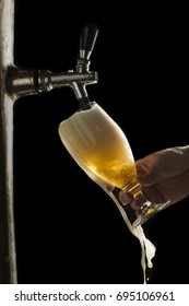 Draft beer overflows from the glass on the dark background
