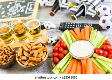 Draft beer and salty snacks on the table for soccer party.