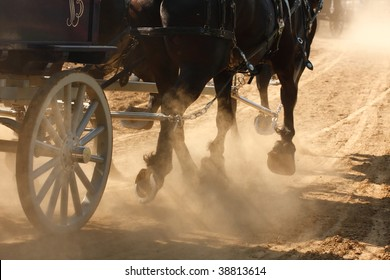 Draft horses pulling a wagon through a dusty field.