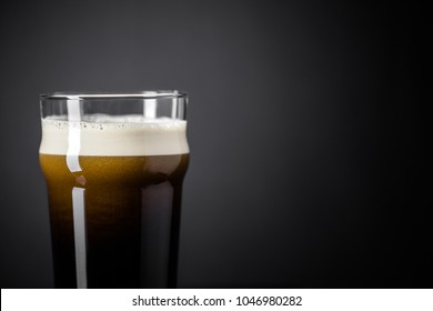 Draft Nitrogen Fresh and Creamy Black Irish Stout Beer Pint over Black Background in Studio.