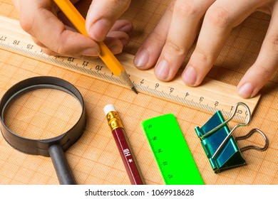 draftsman draws on a ruler on the graph paper