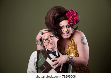 Drag queen holds a Caucasian nerd on green background