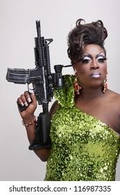 Drag queen wearing a green gown holding an assault rifle.