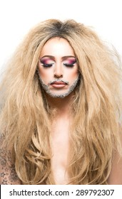 Drag queen with wild cavewoman hair and fabulous make up with glittery beard and with naked chest and white background.