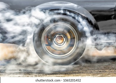 Drag racing car burns rubber off its tires in preparation for th