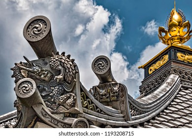 Dragon Architectural Decoration with Triple Headed Oni Ogres and Gold Bulb on top of Historic Japanese Temple (Kyoto, Japan).