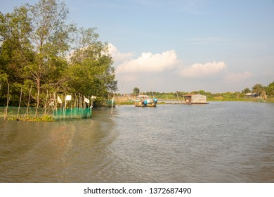 Dragon boat tied along house in floating rural village in Mekong River Delta in Vietnam.