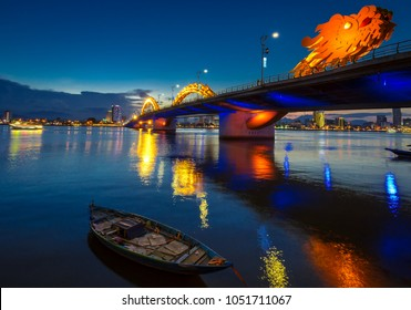 Dragon Bridge in DaNang all lit up, taken in the evening just after sunset. The bridge and city lights reflecting on the large river.