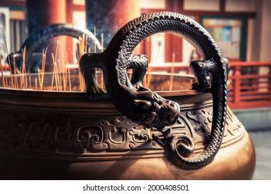 Une déité du dragon dans un bol de culte à la chandelle au temple asiatique de la Relique des Dents de Bouddha à Singapour, dans le quartier chinois