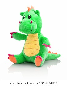 Dragon plushie doll isolated on white background with shadow reflection. Dragon plush stuffed puppet on white backdrop. Dino plushie toy. Green color stuffed dinosaur toy. Lizard toy sitting on white