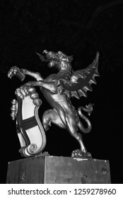 Dragon statue in London, United Kingdom. Dragon with shield on dark sky at night. Coat of arms. Famous tourist attraction. Art and design concept.