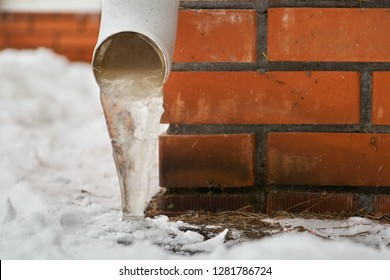 Drain pipe with frozen stream of water near brick wall of a cottage outdoors in winter