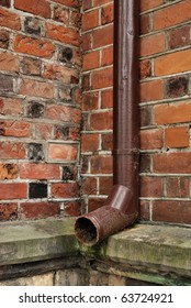 A drain pipe on the side of an old wall building.