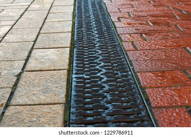 drainage paved with red and yellow tile, drainage on the sidewalk, the grille is a rain gutter on the sidewalk