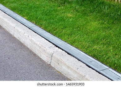 drainage system along an asphalt road with a stone curb and grill for rainwater in a green lawn.