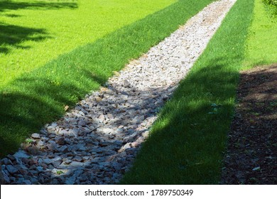 drainage, a drainage system in a Park area, a waterway overgrown with lawn and paved with stones, an Aqueduct between nature and the road. stone water drains in a grass garden field. Lawn and plant