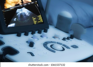 Drak and Blurry Medical ultrasound machine with 3D/4D image and linear probes in a hospital diagnostic room. Modern medical equipment, preventional medicine and healthcare concept.